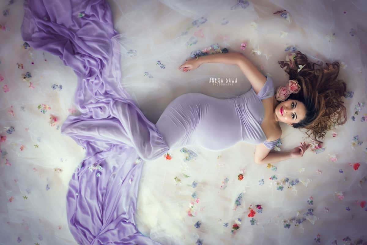 best_pregnancy_photographer_delhi_gurgaon_lavender_outfit_white_floral_backdrop_anega_bawa