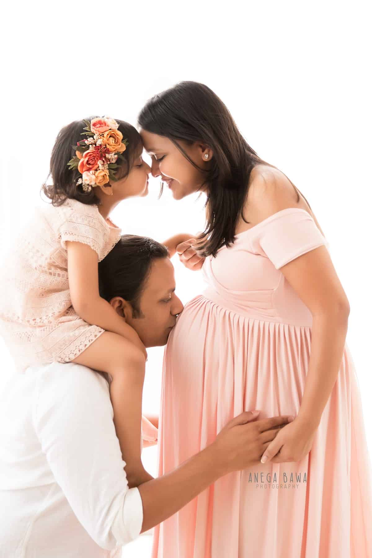 best_pregnancy_photography_delhi_gurgaon_family_pink_outfit_white_background_anega_bawa