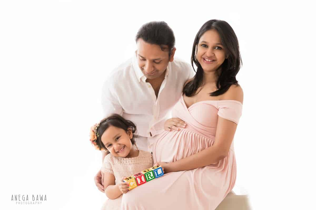 best pregnancy photography delhi noida husband daughter pink outfit white background anega bawa