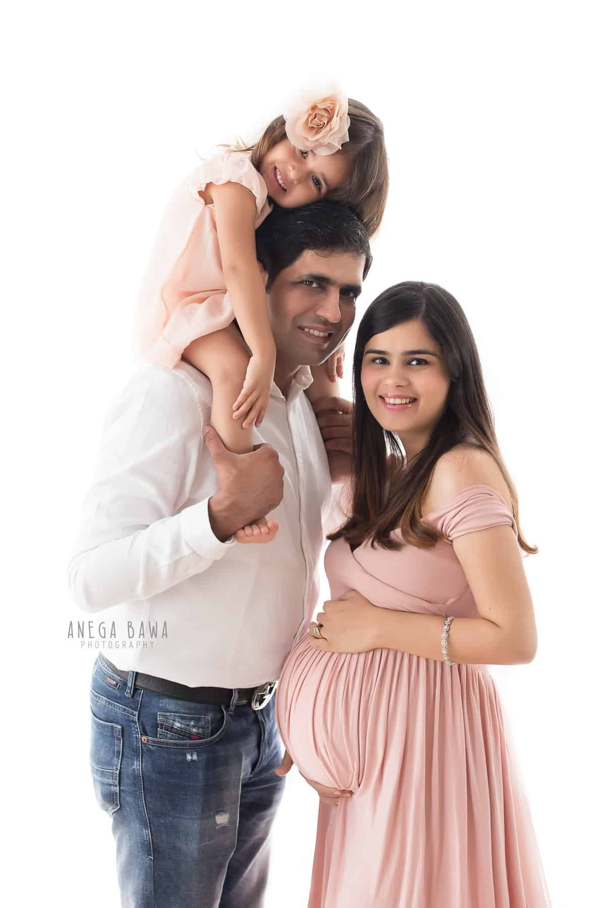 top_pregnancy_photoshoot_delhi_gurgaon_husband_daughter_pink_outfit_white_backdrop_anega_bawa (1)