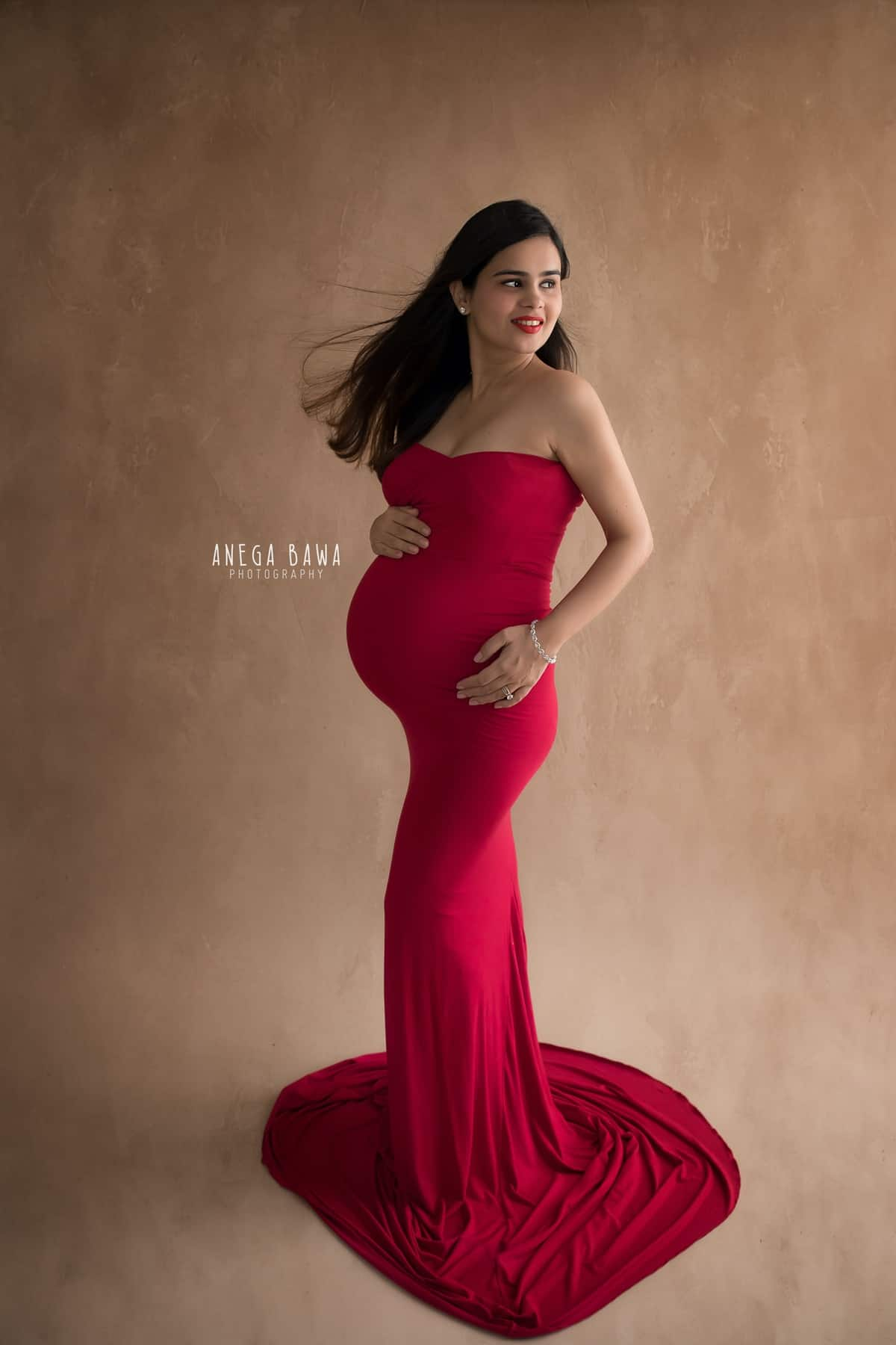 top_pregnancy_photoshoot_delhi_noida_red_outfit_beige_painted_backdrop_anega_bawa (1)