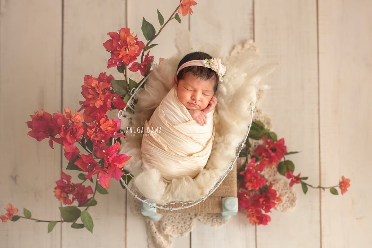 247501-white-wooden-background-pink-floral-newborn-photography-delhi-12-days-baby-girl-photoshoot-gurgaon-anega-bawa