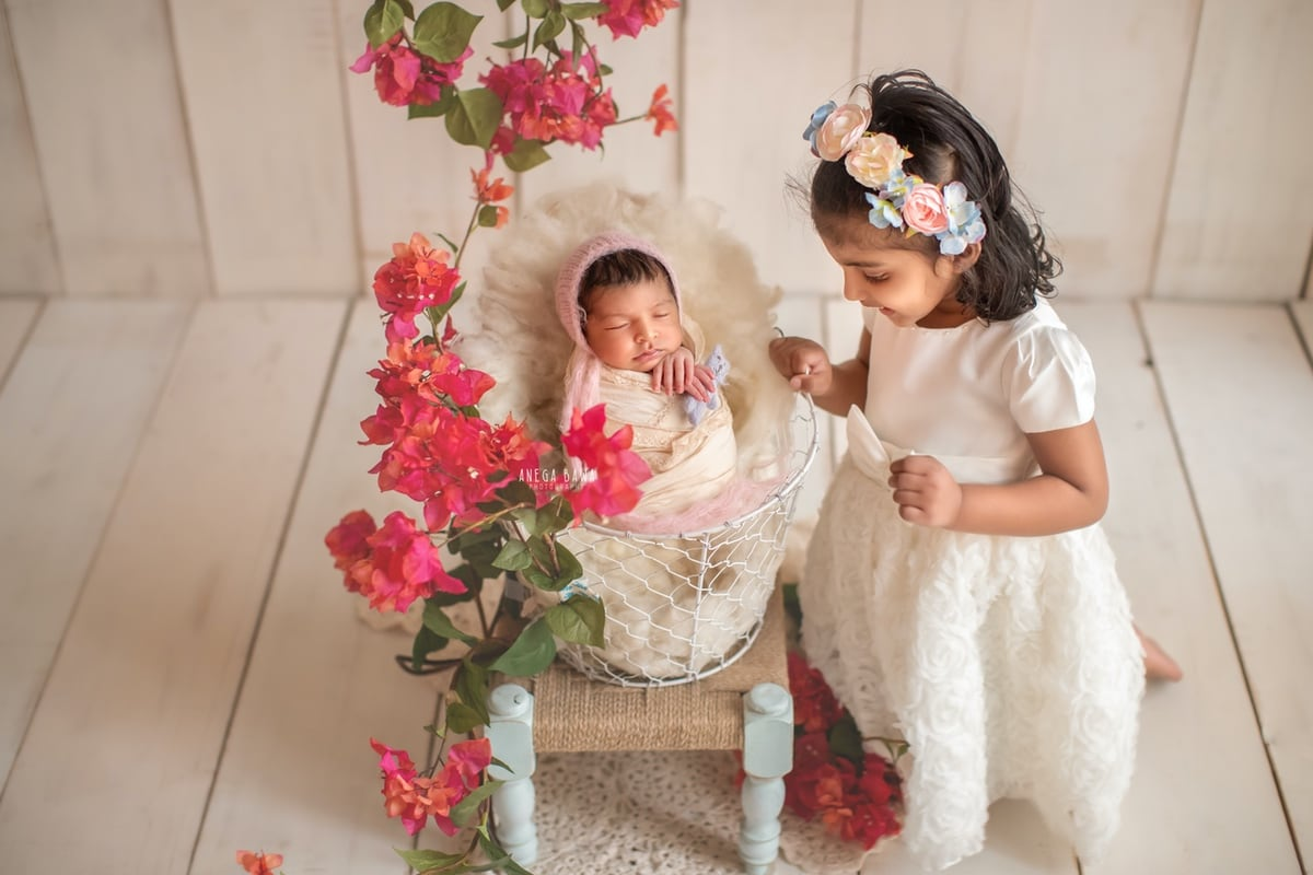 247505-white-wooden-background-pink-floral-newborn-and-sister-photography-delhi-12-days-baby-girlphotoshoot-gurgaon-anega-bawa