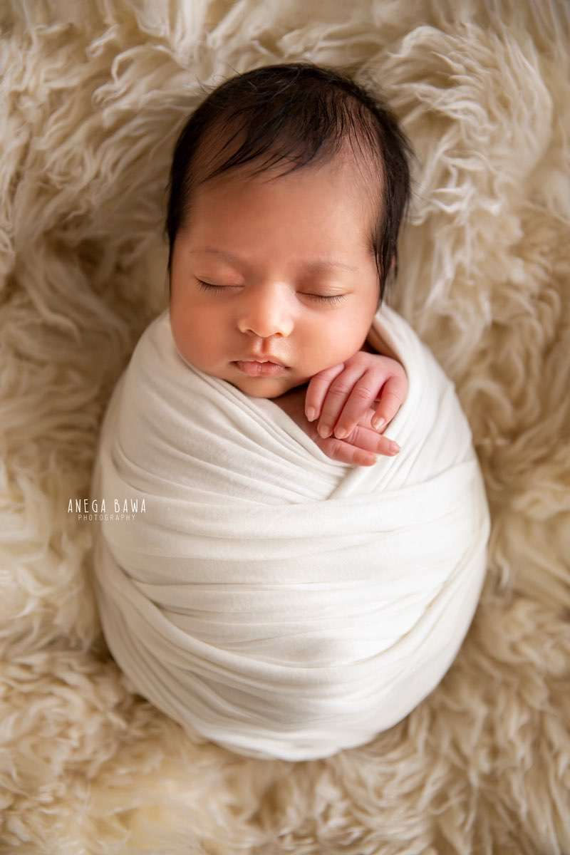 250803-white-background-white-wrap-floral-newborn-photography-delhi-14-days-baby-photoshoot-gurgaon-anega-bawa